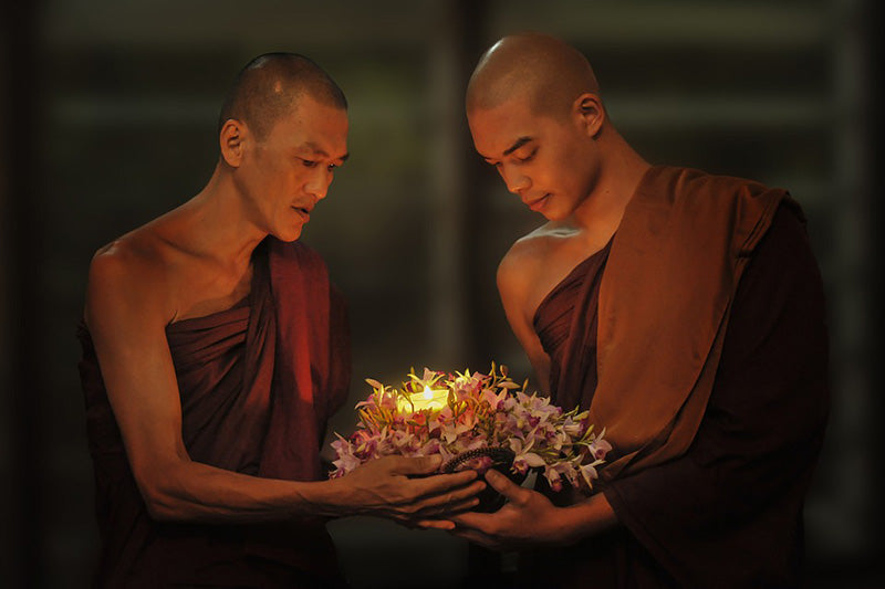 Monks praying while holding a candle together