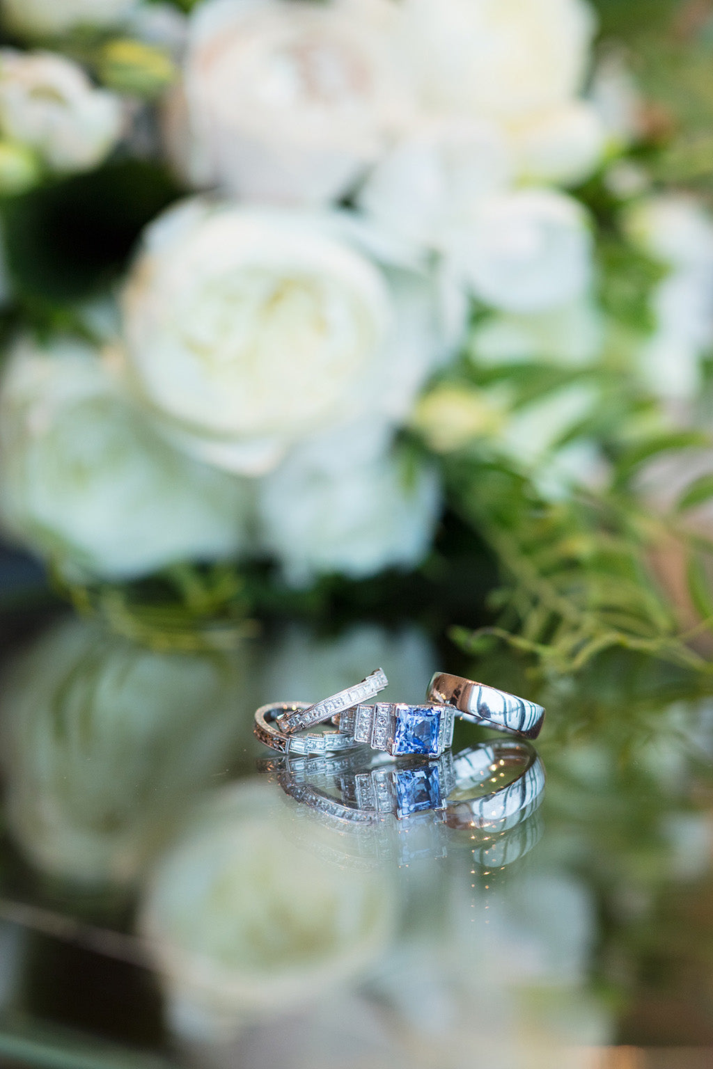 Wedding rings with wedding flowers in background