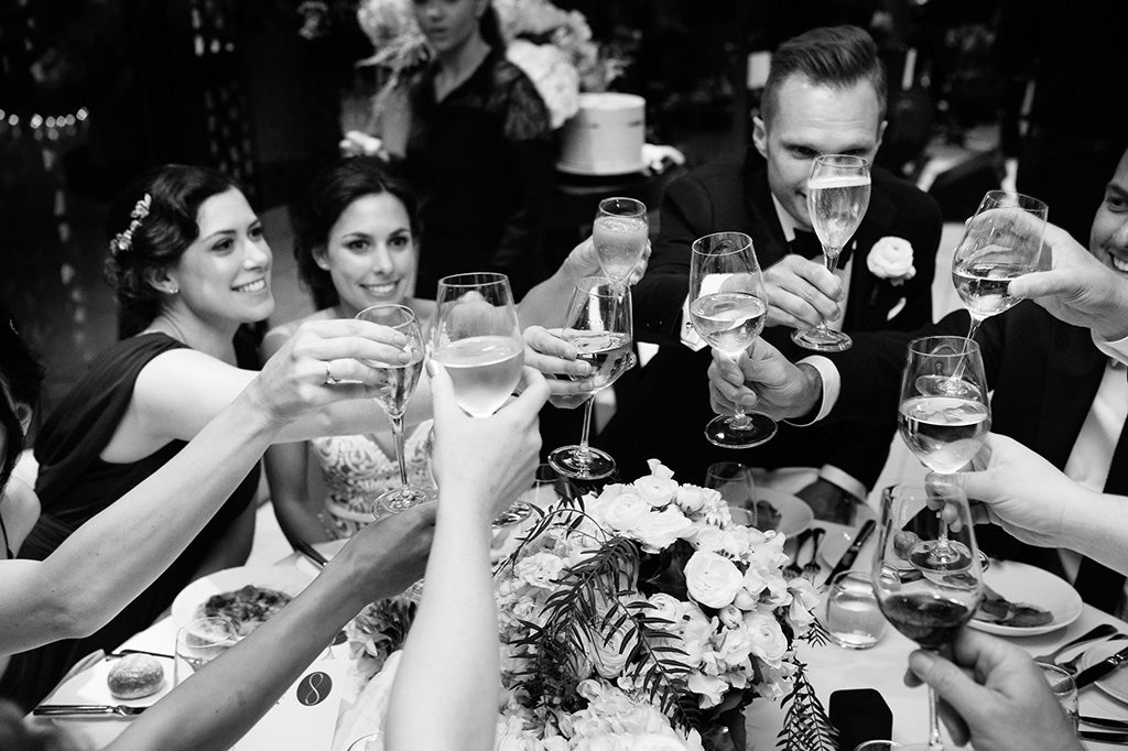 Wedding party toasting around table with wedding flowers as centrepiece