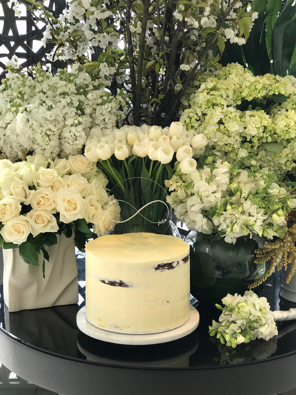 Wedding cake surrounded by white wedding flowers