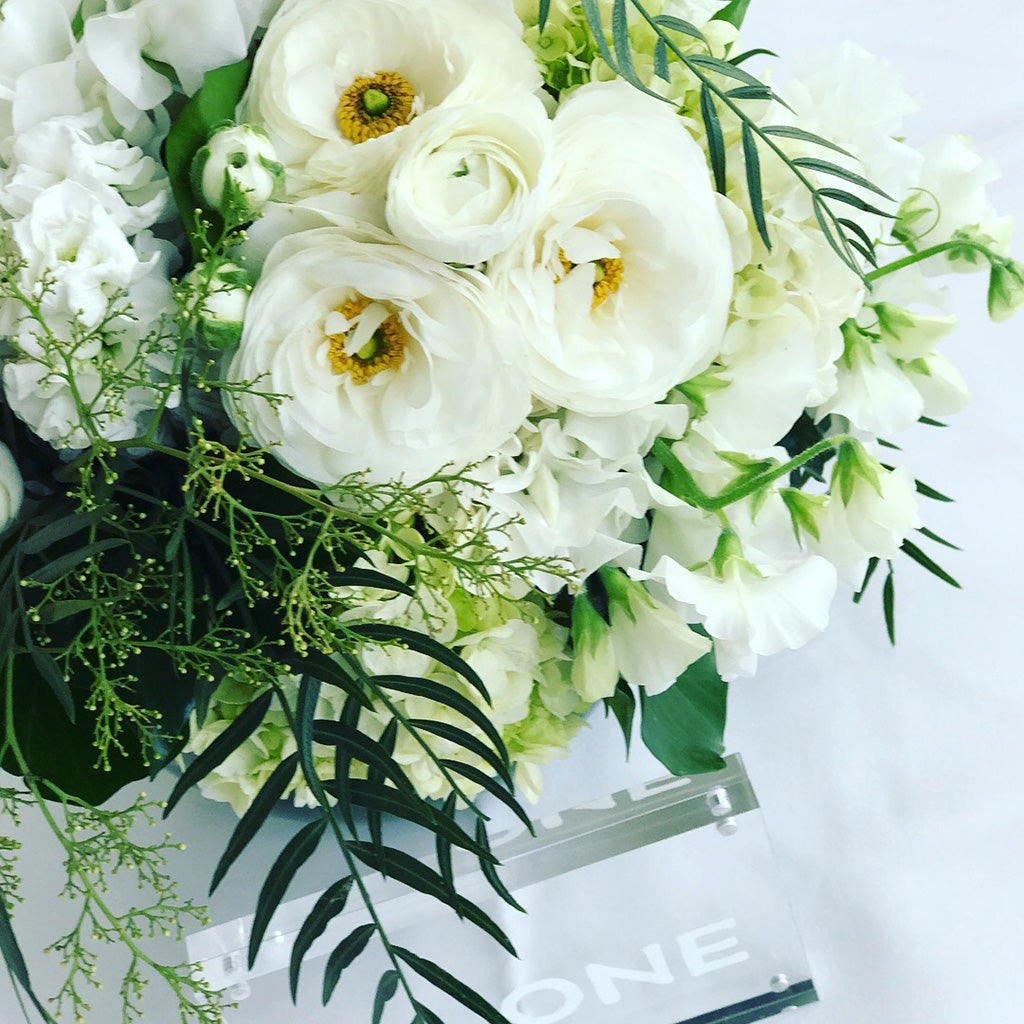Table centrepiece of white wedding flowers
