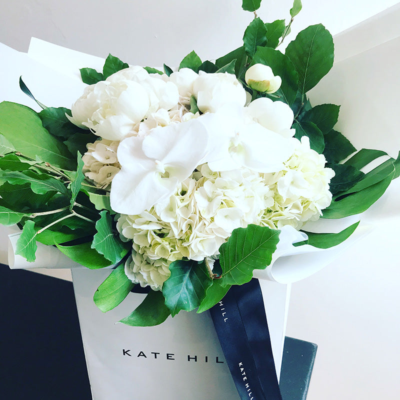White birthday bouquet in flower bag by Kate Hill