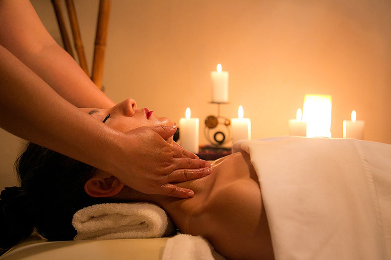 Woman being massaged with candles burning