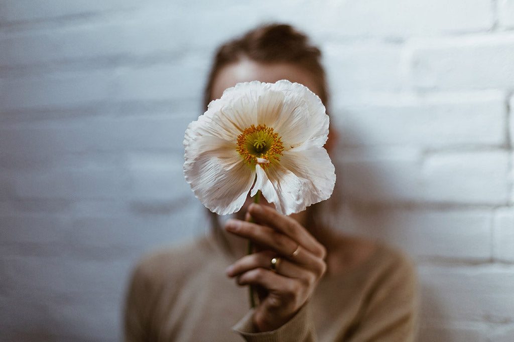 Girl holding poppy flower showing pollen