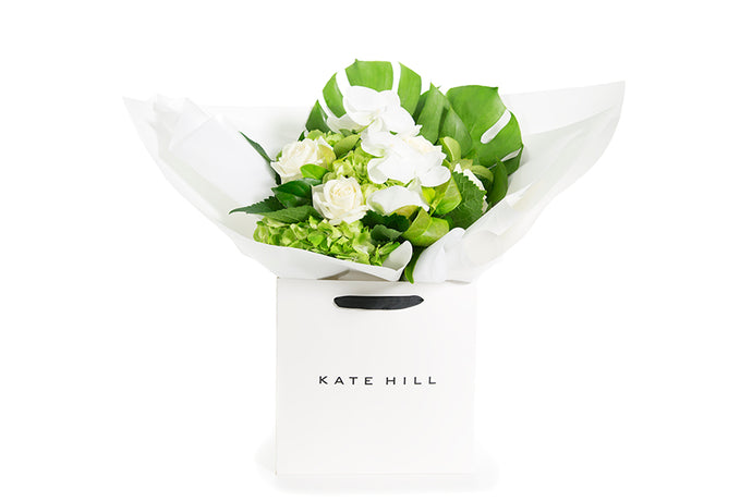 White phalaenopsis orchids and green foliage bouquet wrapped in white paper and seated in a Kate Hill flower bag | Kate Hill Flowers