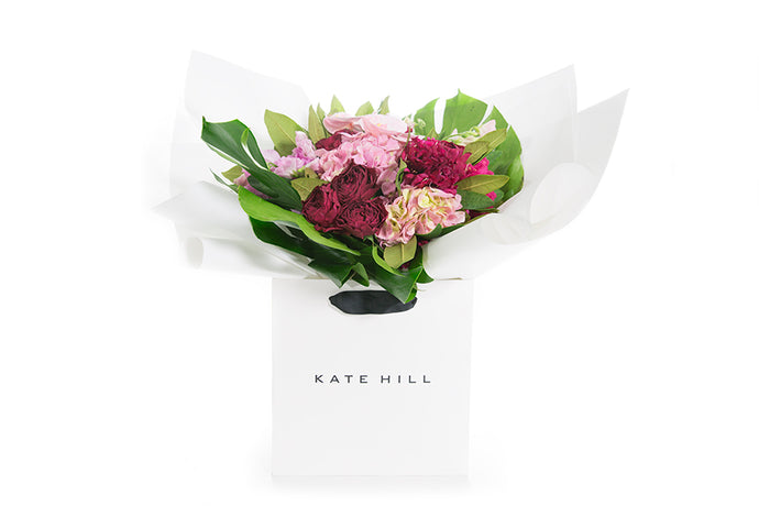 Flower bouquet full of pink blooms wrapped in white paper and seated in a Kate Hill flower bag | ARIA Flower Bouquet | Flowers & Plants Store | Kate Hill Flowers