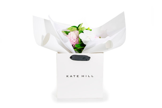 Posy of flowers and green foliages wrapped in white paper and seated in a flower bag