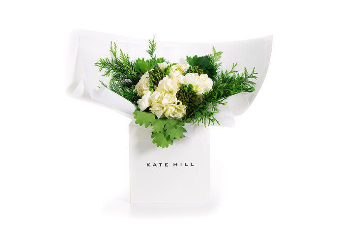 A Christmas festive style bouquet featuring white flowers and green foliage, all gift wrapped in white paper and seated in a Kate Hill gift bag