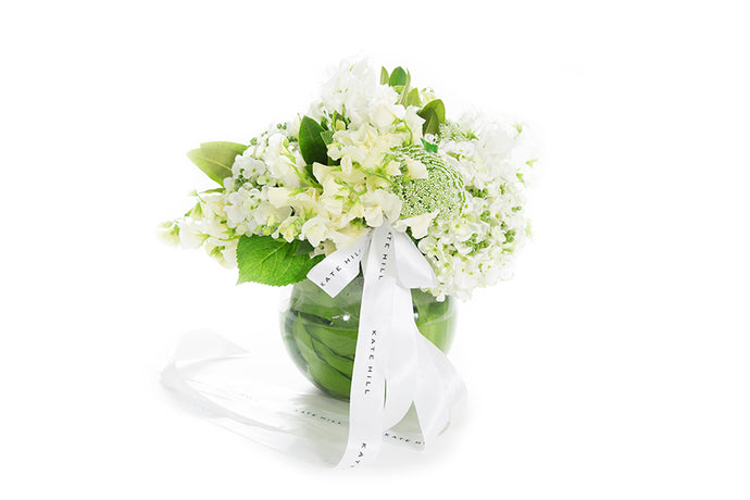 Mix of white seasonal flowers designed into a ball vase