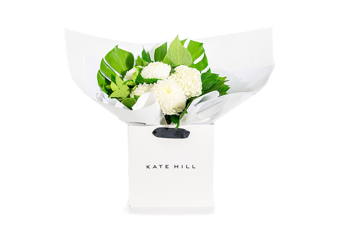 White flower bouquet with green foliage in gift