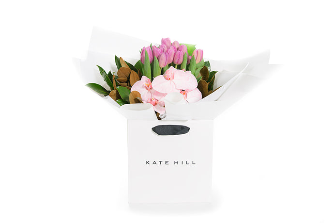 Flower bouquet featuring pink tulips and orchids gift wrapped in white paper and seated in a Kate Hill flower bag