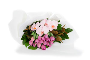Flower bouquet featuring pink tulips and orchids gift wrapped in white paper