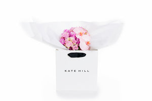 A variery of pink flowers all gift wrapped in white paper and seated in a Kate Hill Flowers gift bag
