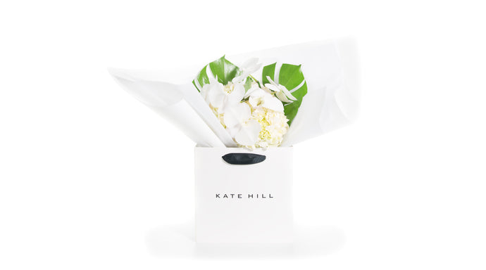 A mix of white flowers gift wrapped and placed into a Kate Hill gift bag