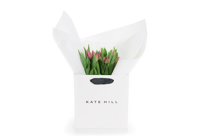 Grouping of tulip flowers in white gift wrapping and a Kate Hill Flowers gift bag