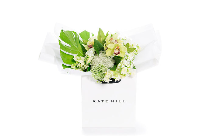 Flower bouquet featuring green and white blooms gift wrapped in white paper and a Kate Hill flower bag