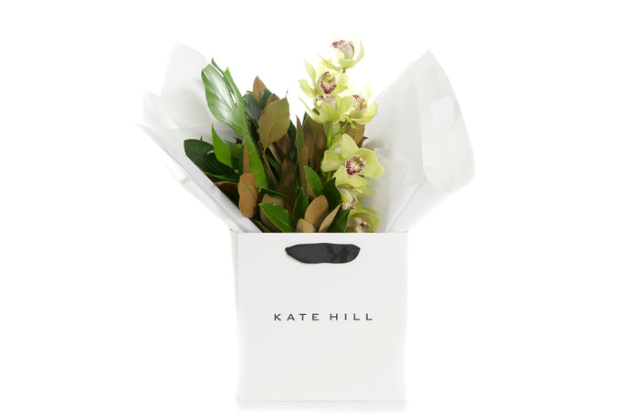 Green foliage and cymbidium orchid flowers bouquet gift wrapped in white paper and seated in a Kate Hill Flowers gift bag