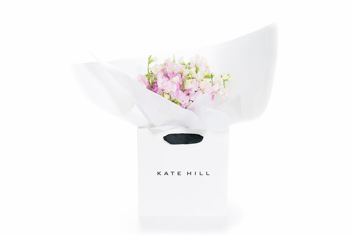 Pink flower arrangement gift wrapped in white paper and seating in a Kate Hill Flowers gift bag