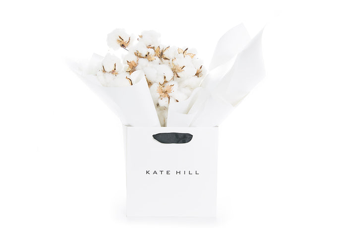 White cotton flowers gift wrapped and seated in a Kate Hill Flowers gift bag