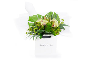 Flower bouquet featuring green flowers and green textural foliage all wrapped in luxurious white paper and seated in a Kate Hill flowers gift bag