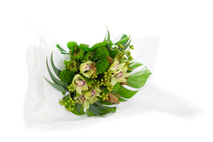 Flower bouquet featuring green flowers and green textural foliage all wrapped in luxurious white paper
