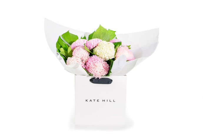 Flower bouquet consisting of pink disbud flowers in white flower bag