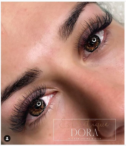 Captured top view photo of a lash client looking at the camera with her tinted eyebrows and a  volume eyelash extension set