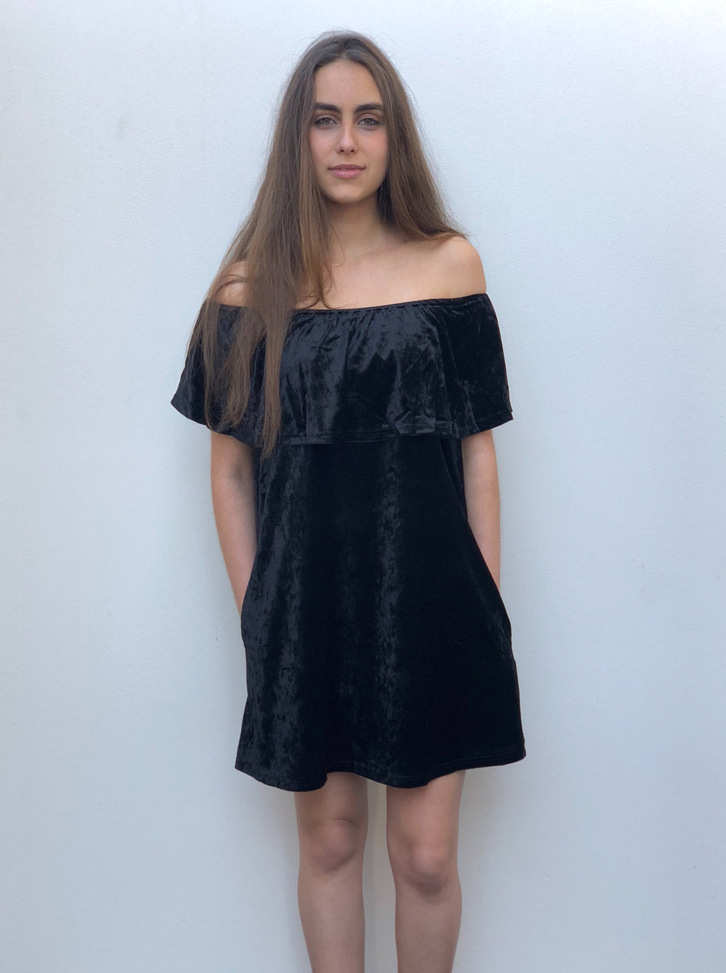 Black off-the-shoulder velvet dress with frill detailing on the chest and pockets.
