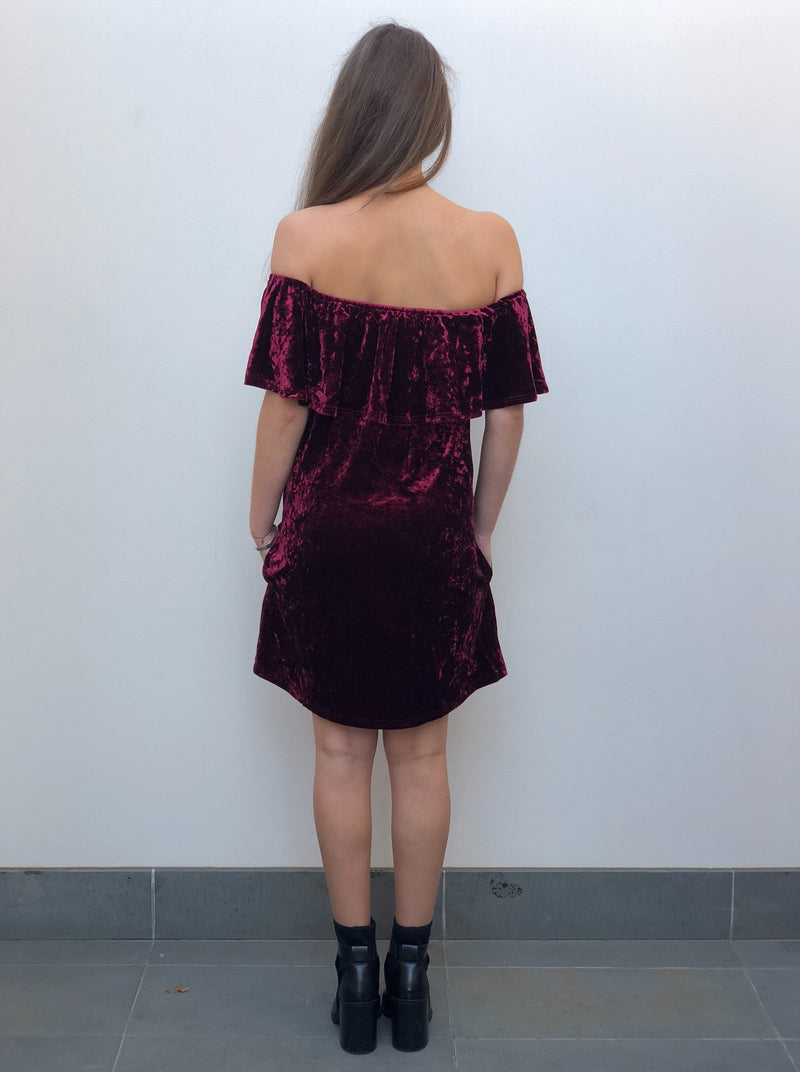 Burgundy off-the-shoulder velvet dress with frill detailing on the chest and pockets.