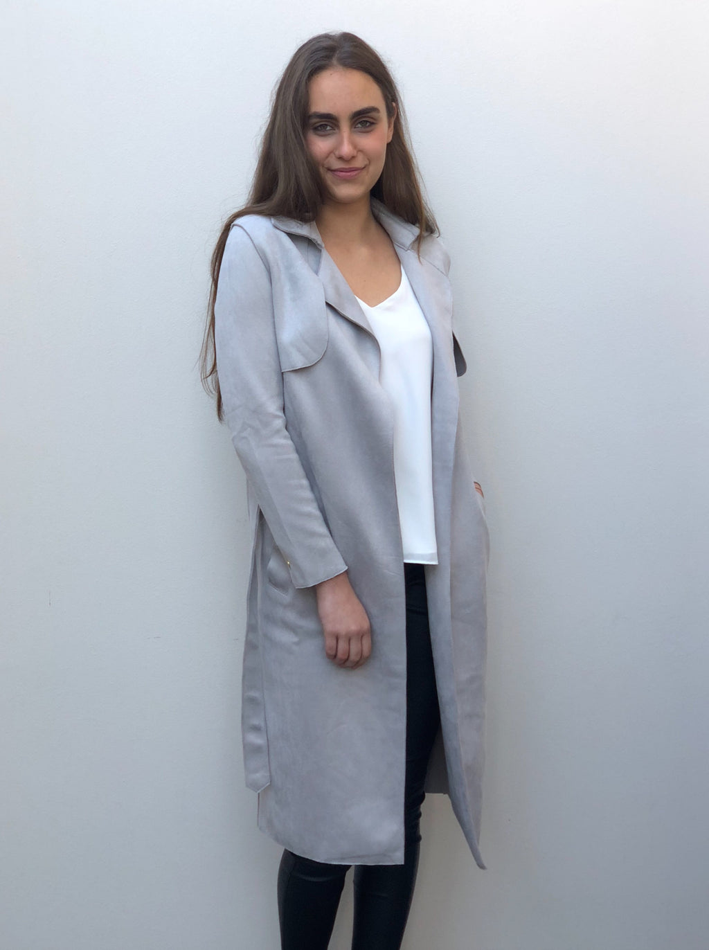 Grey coat featuring gold hardware, angled pockets and a waist tie.
