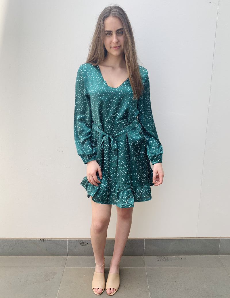 This emerald polka dot dress features a v neck, long sleeves, pockets, a waist tie and ruffle hem.
