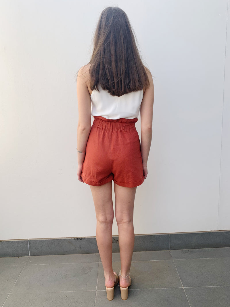Vibrant rust shorts featuring a high waisted fit, stretch ruffled waist detailing and side pockets.