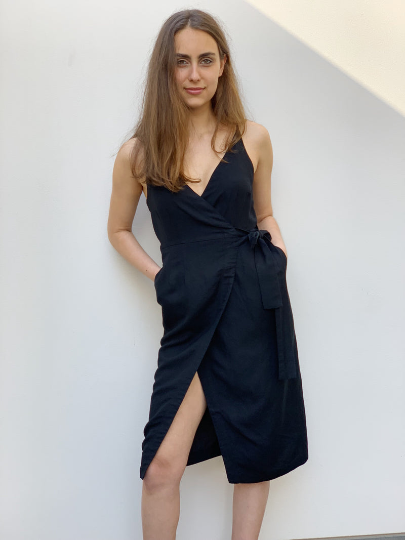 Black wrap dress featuring adjustable spaghetti straps, a side tie and side seam pockets.