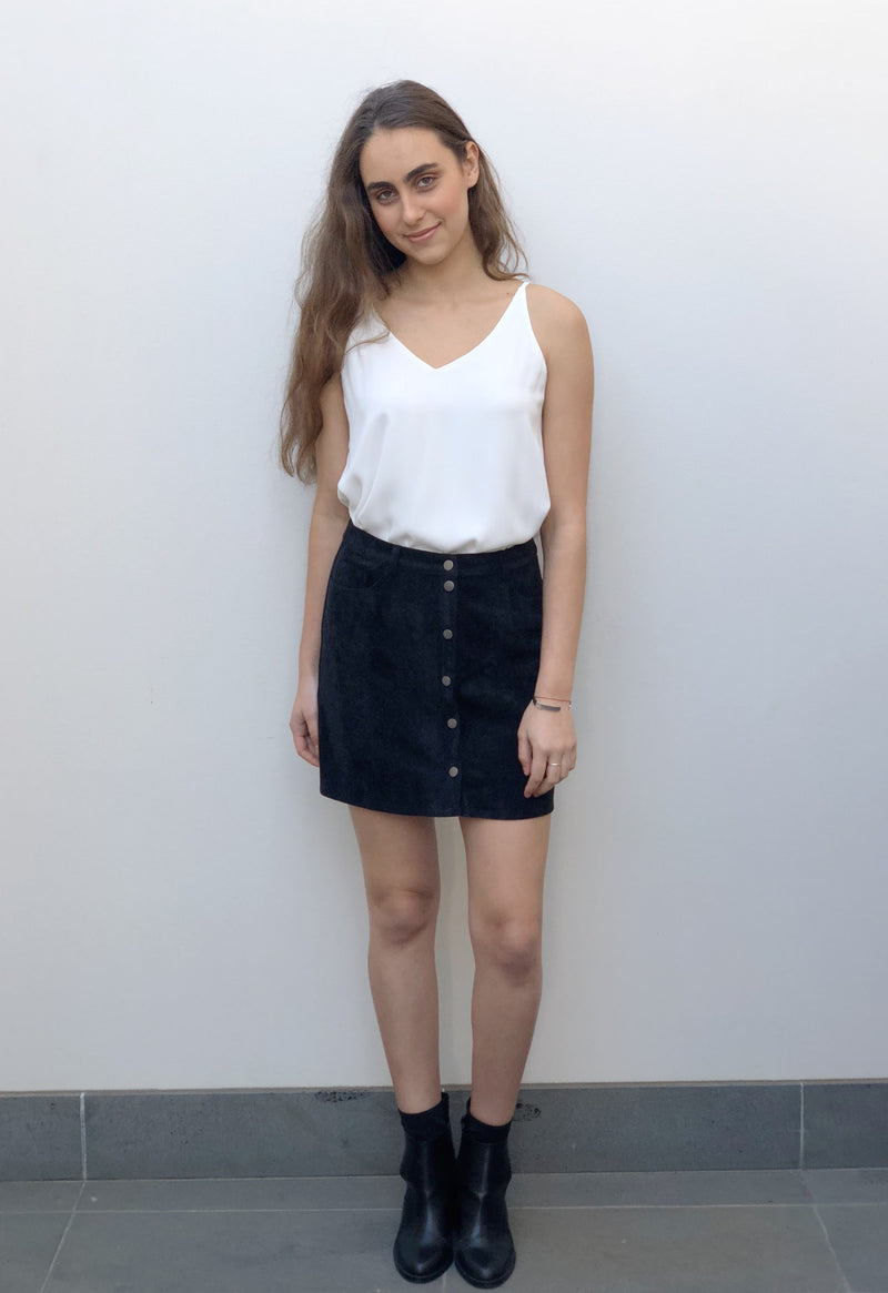 Black mini skirt featuring a popper button front and pockets.