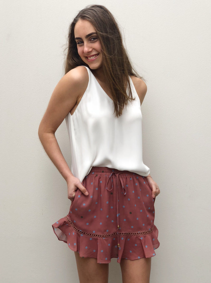 Rust spot print skirt featuring an elastic waist, side pockets, tie on waist, frill detail at hem.