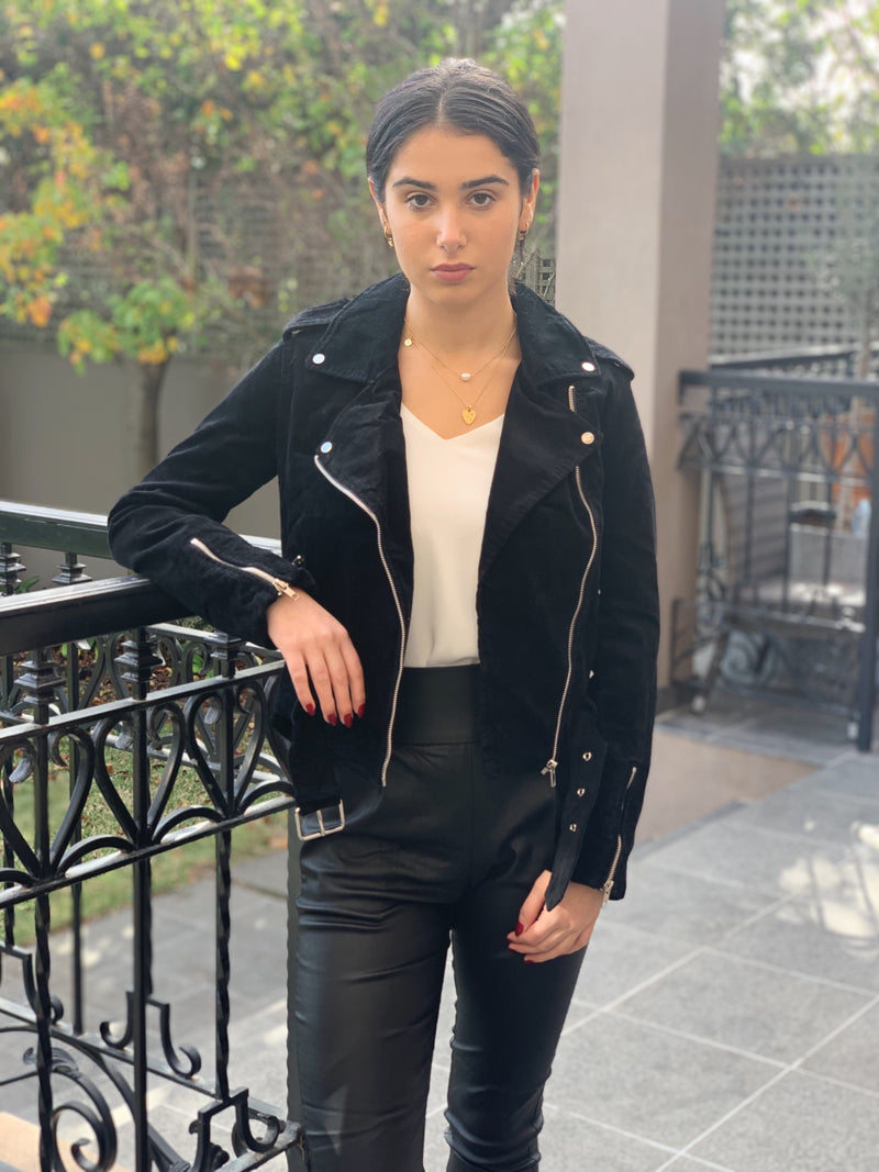 Black corduroy biker jacket featuring long sleeves with zipper detail, zip front and pockets.