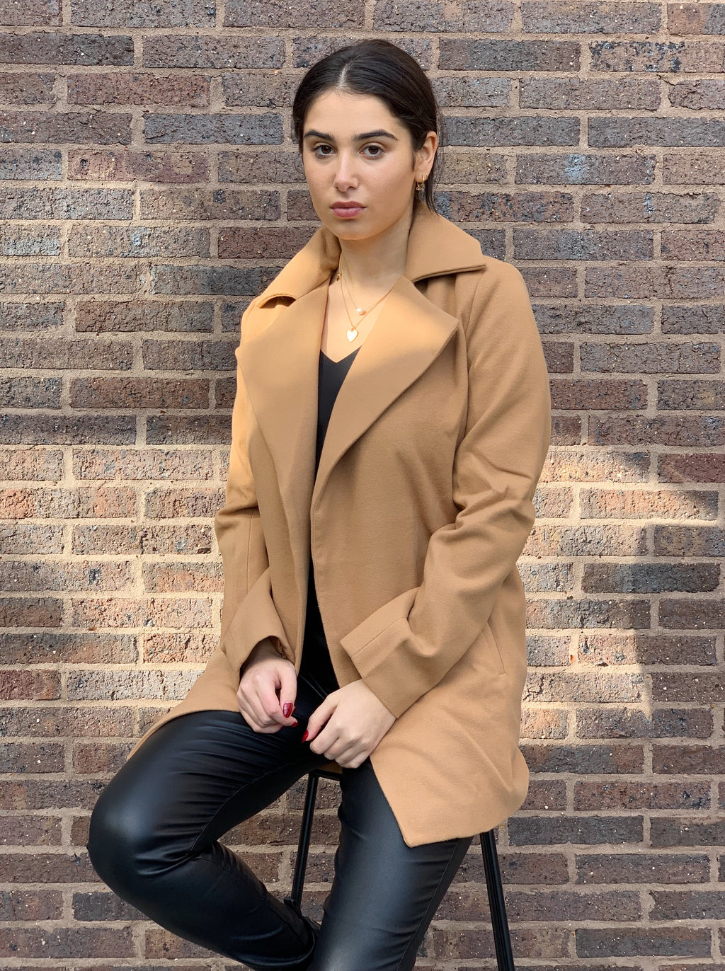 Mid-length camel coat featuring an exaggerated collar and lapel, side pockets and is lined..