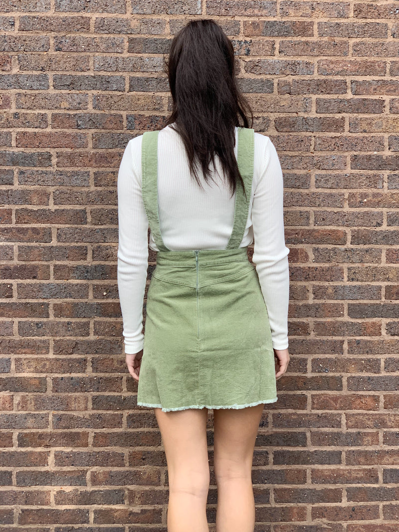 This gorgeous corduroy pinafore features a square neckline, shoulder straps and pockets.