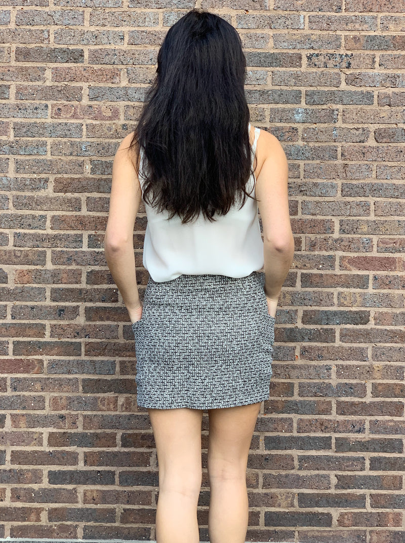 Black and white tweed style mini skirt featuring a front zip and pockets.