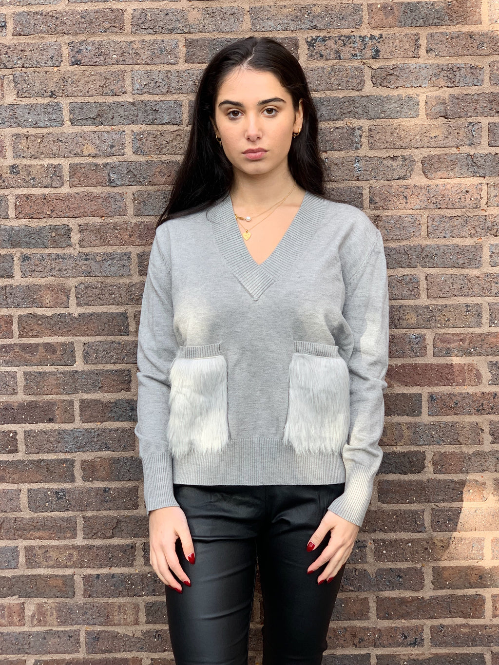Grey knit featuring a v neck, long sleeves and super soft fur pockets.