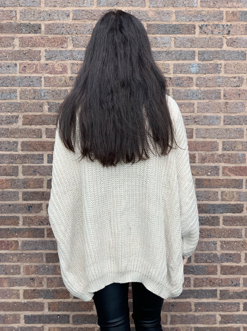 Oatmeal coloured cardigan made from soft fabric with roomy pockets and is an oversized fit.