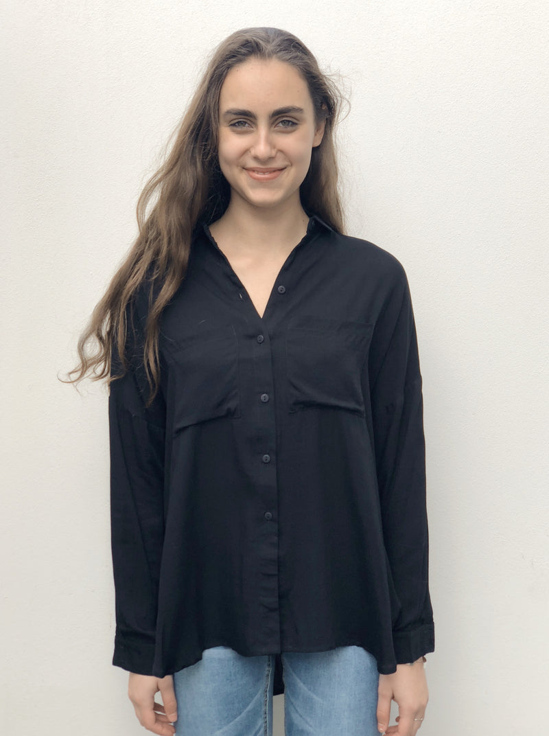 Black shirt featuring chest pockets and a dipped curved hemline.