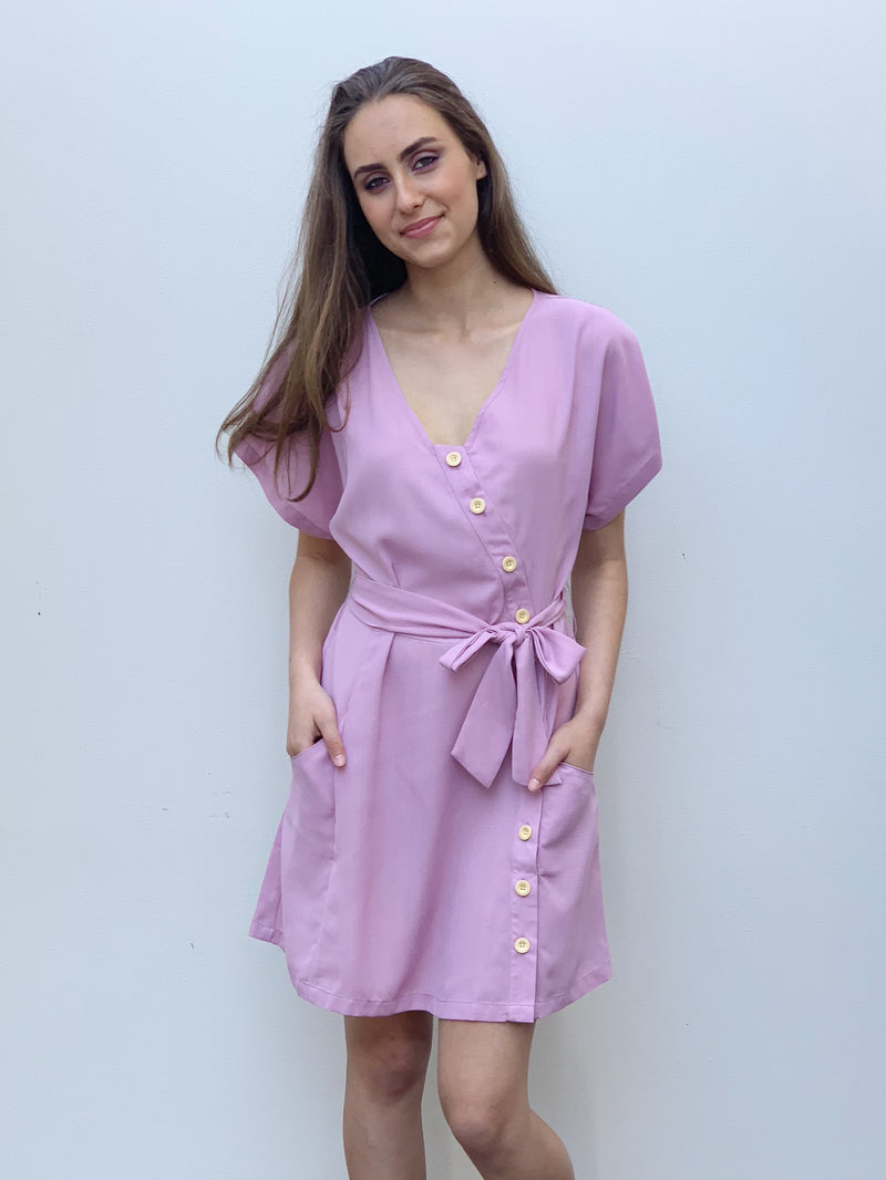 Lilac short sleeve dress with cream buttons down the front, a v-neckline, waist tie and pockets