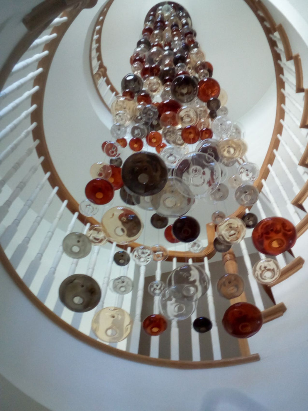 20 feet tall bespoke stairwell chandelier with colored glass bubbles