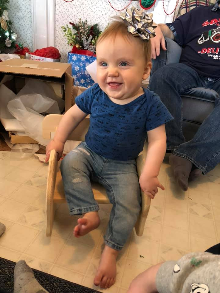 Ezekiel with a bow on his head sitting in a Thorpe Toys hand-crafted, wooden, Combination Chair with a BIG grin on his face.