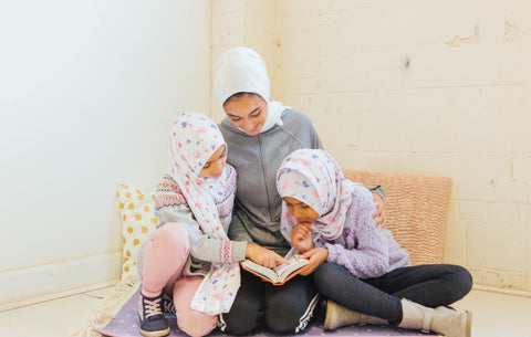 mom reading quran with kids girls in hijab