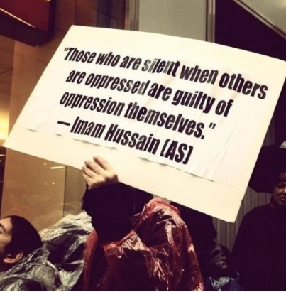 """A sign at a protest states, """"Those who are silent when others are oppressed are guilty of oppression themselves."""" - Imam Hussain (AS)"""