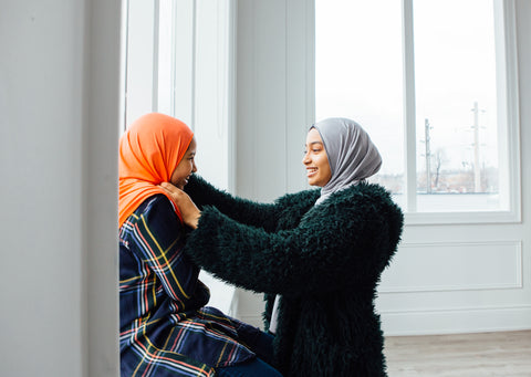 two sisters wearing an orange and grey hijab talking to each other in a home