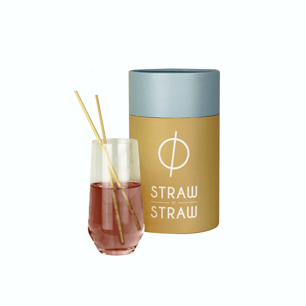 Straw of Straw by Straw in a glass with a box of Straw by straw on the background.