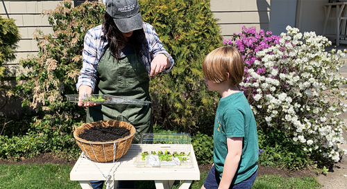 An adult Ferry-Morse gardener showing a young gardener how they're going to put together a statement hanging basket.
